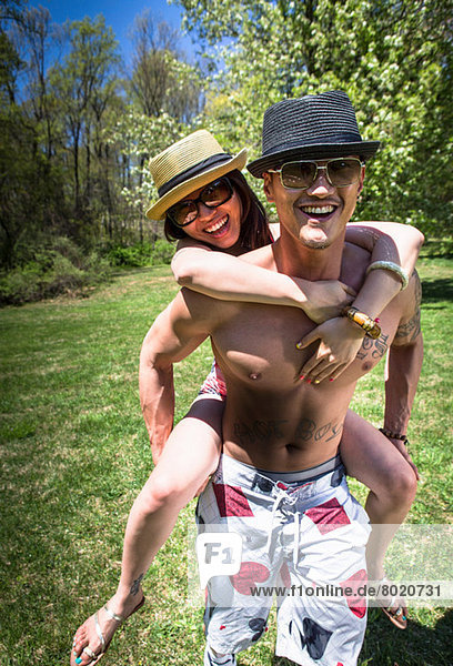 Couple in garden  man giving woman piggy back