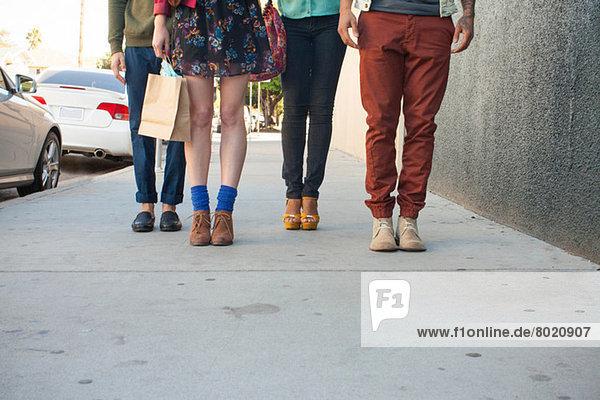 Vier junge Erwachsene auf dem Bürgersteig stehend  niedriger Abschnitt