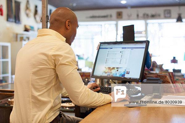 Ladenbesitzer mit Computer im Vintage-Shop