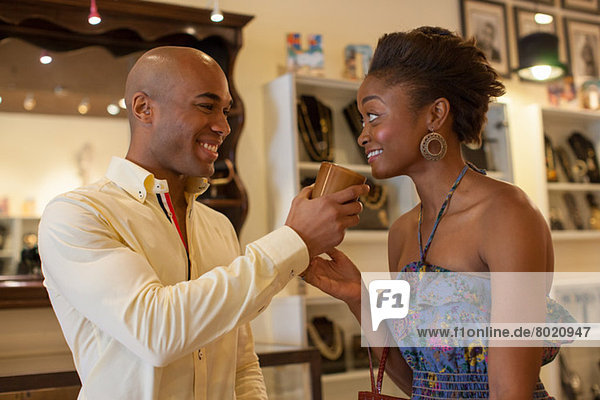 Young couple holding ornament in vintage shop