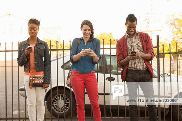 Drei Freunde  die Handys am Metallzaun benutzen.