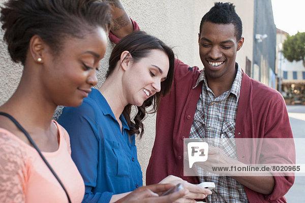 Drei Freunde  die Handys benutzen