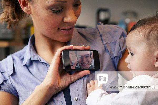 Baby Mädchen beobachtet Vater auf Videoanruf  Mutter mit Smartphone