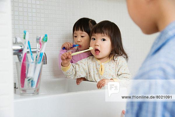 Zwei Mädchen beim Zähneputzen am Waschbecken