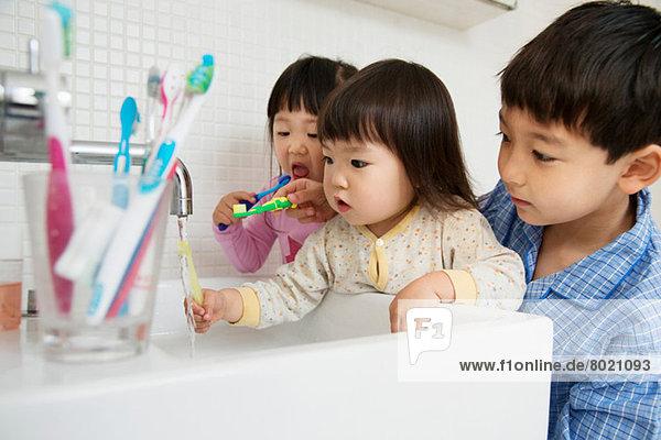 Bruder hilft Schwestern beim Zähneputzen