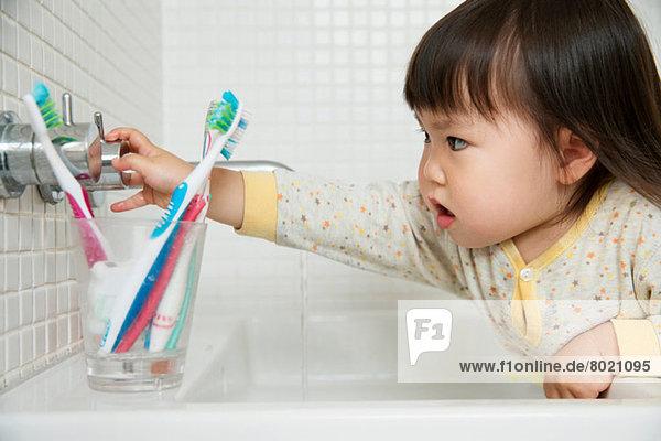 Close up von Mädchen Kleinkind Drehen Badezimmer Waschbecken Armaturen