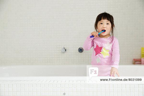 Weibliches Kleinkind in der Badewanne stehend  Zähne putzend