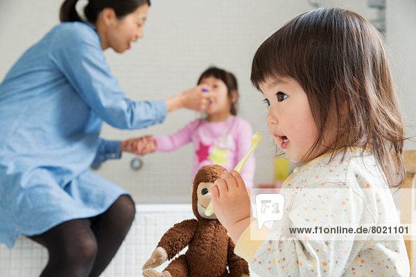 Kleinkind mit Kuscheltier und Zahnbürste