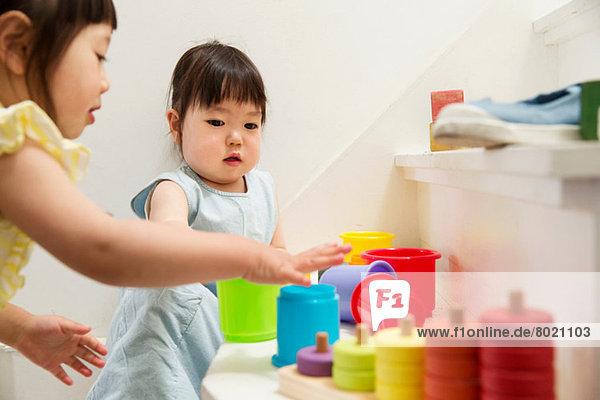Zwei junge Schwestern spielen mit Spielzeug auf der Treppe