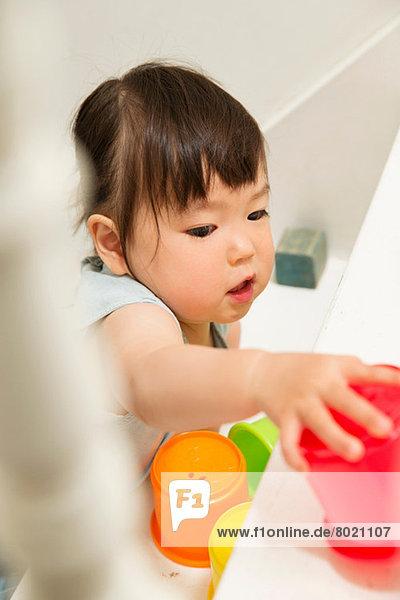 Weibliches Kleinkind beim Spielen mit Spielzeug auf der Treppe