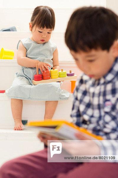 Geschwister spielen mit Spielzeug auf der Treppe