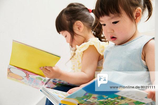 Zwei junge Schwestern beim Betrachten von Bilderbüchern