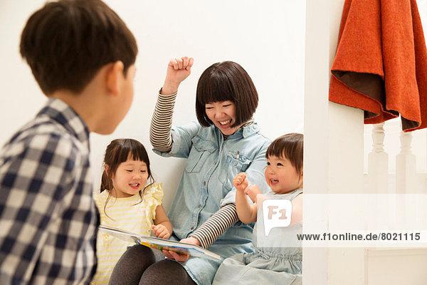 Mutter und Kinder lachen über das Märchenbuch