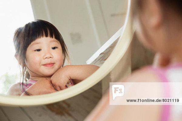 Kleinkind schaut in den Spiegel  während es sein Kleid befestigt.