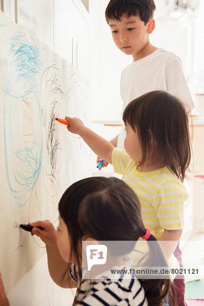 Bruder und zwei junge Schwestern beim Zeichnen