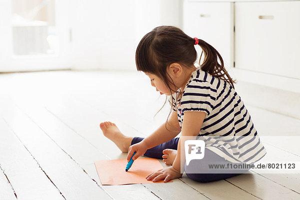 Kleinkind auf Bodenzeichnung sitzend