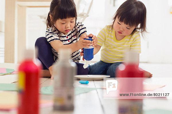 Zwei junge Schwestern  die Farbe aus den Flaschen quetschen.