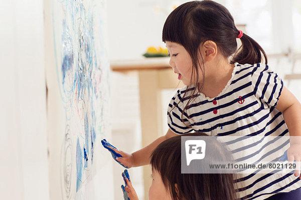 Zwei junge Schwestern  die Handabdrücke malen.