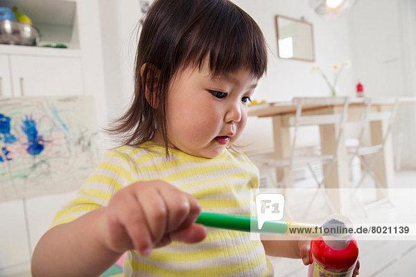 Weibliches Kleinkind mit Pinsel und Farbe