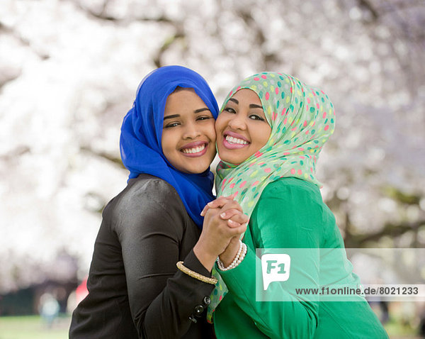 Portrait of two young females in park dancing together
