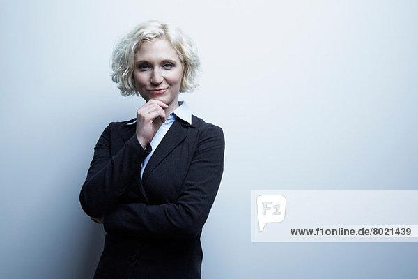 Studio-Porträt der Geschäftsfrau mit Hand am Kinn