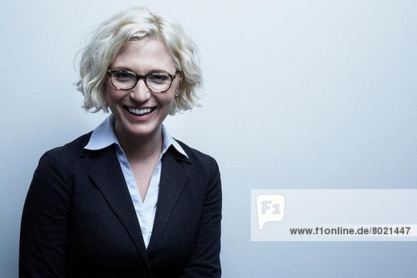 Studio-Porträt der blonden Geschäftsfrau lächelnd