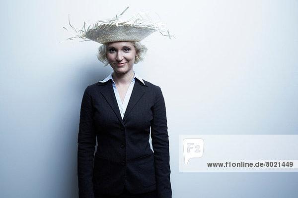 Studio-Porträt einer blonden Geschäftsfrau mit Strohhut