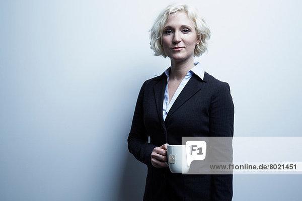 Studio-Porträt einer blonden Geschäftsfrau mit einer Tasse Tee