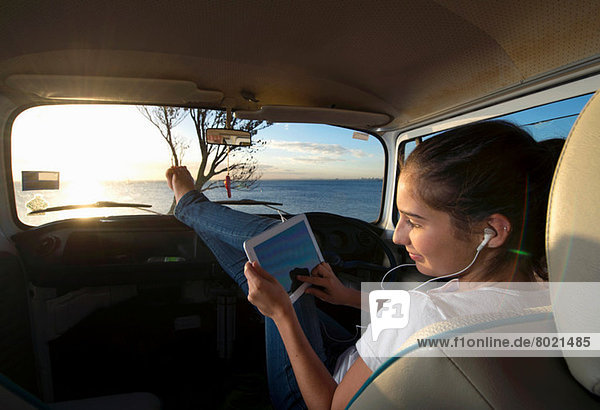 Junge Frau im Wohnmobil mit digitalem Tablett