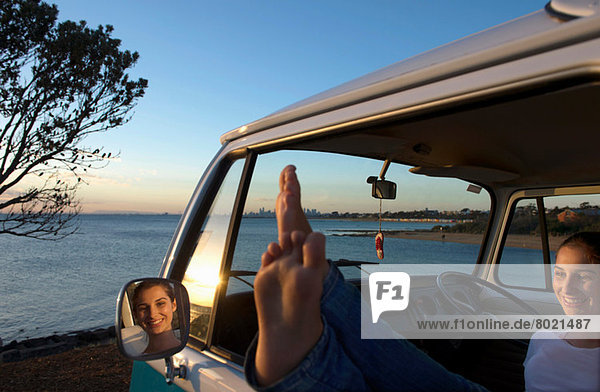 Junge Frau mit erhobenen Füßen am Fenster des Wohnmobils