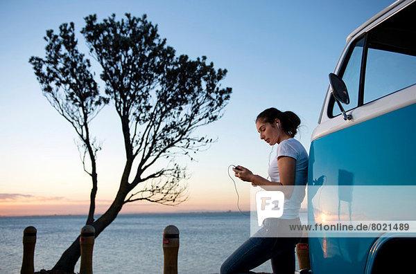 Junge Frau  die sich in der Abenddämmerung auf ein Wohnmobil stützt.