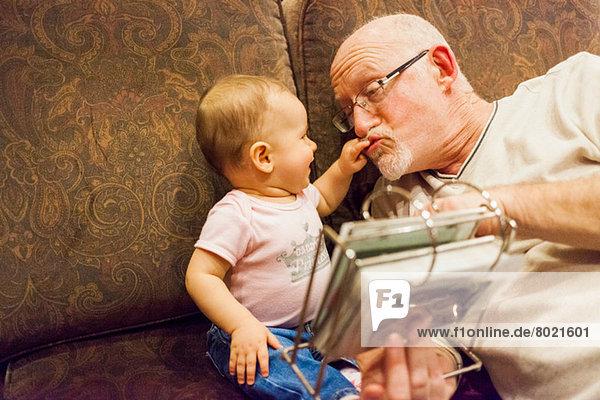 Großvater spielt mit Baby-Enkelin