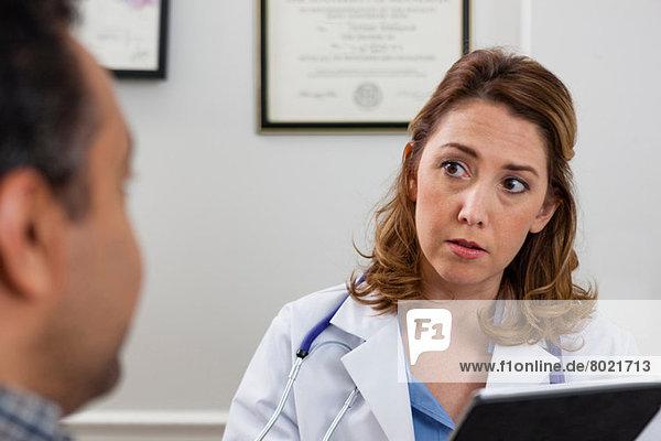 Mittlerer Erwachsener Arzt mit digitalem Tablett und Anhören des Patienten