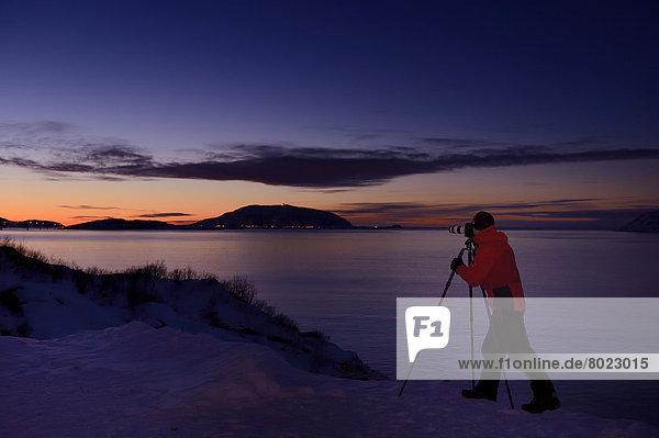Fotograf vor Fjord bei untergehender Sonne