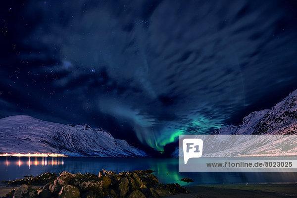 Polarlicht über Fjord mit schneebedeckten Bergen und beleuchteter Ortschaft