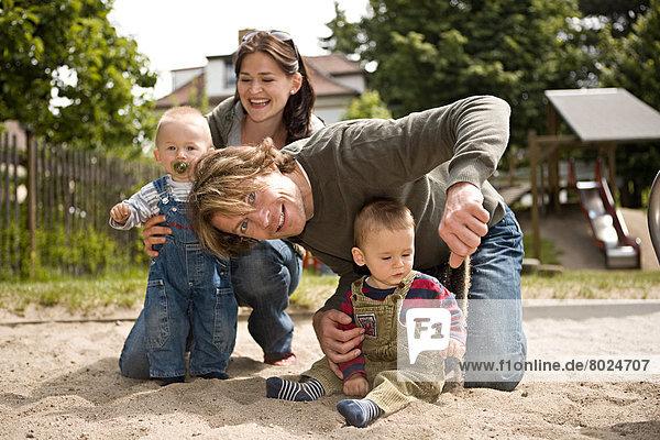 Junge Familie mit zwei kleinen Kindern spielt auf einem Spielplatz