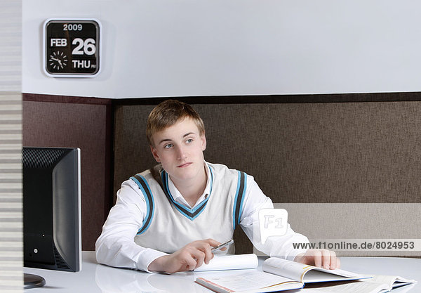 Young man sitting at his desk.
