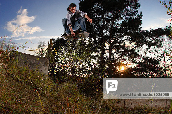 Skateboarder is jumping down a gap.