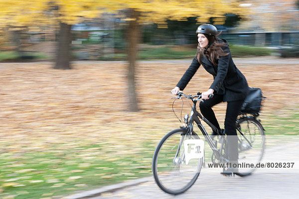 A woman is riding her bicycle in the city of Frankfurt.
