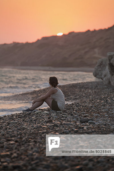 Felsbrocken  Frau  sitzend  Strand  Sonnenuntergang  Ozean  hinaussehen