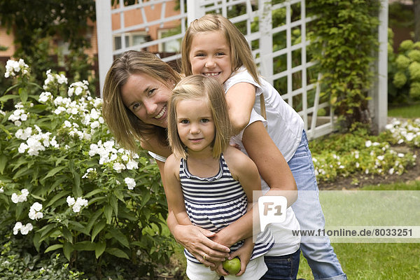 Mother And Her Two Daughters In A Garden  Ontario Canada