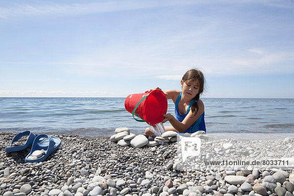 Young girl playing on a pebble beach on the shore of lake ontario Ontario canada