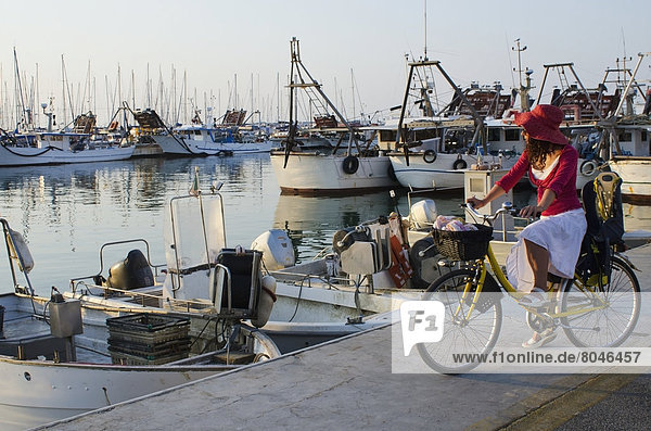 Woman on bicycle looking at sunset in fishing port  Porto San Giorgio  Marche  Italy