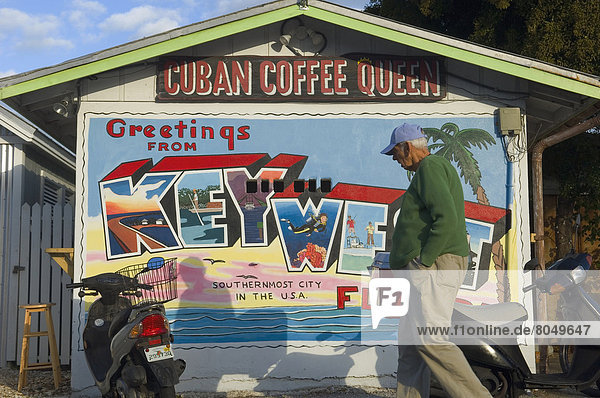 'Old man passing Cuban Coffee Queen shack featuring mural saying ''greetings from Key West''  Key West  Florida Keys  USA'