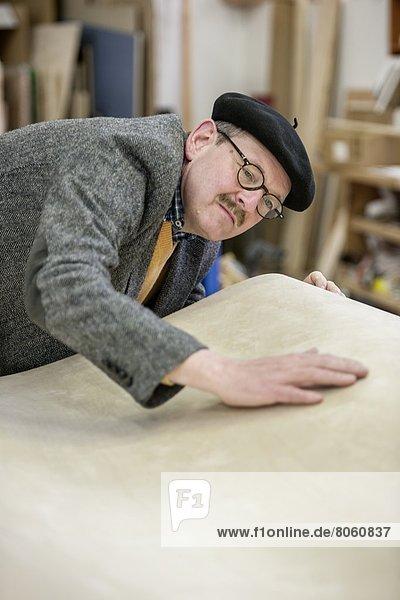 Mann kontrolliert die Oberfläche einer Platte