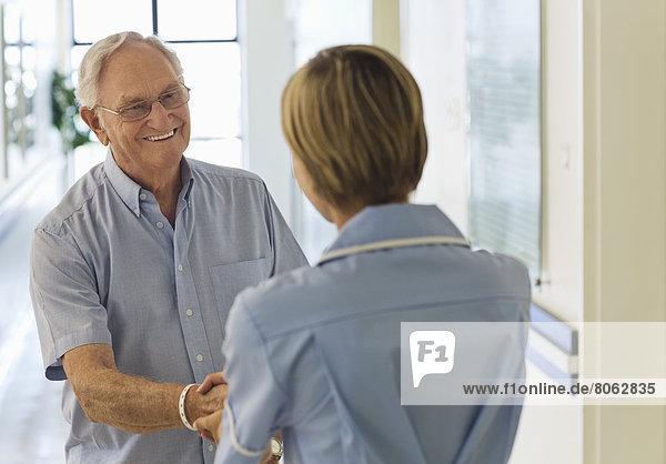 Ältere Patienten und Krankenschwestern beim Händeschütteln im Krankenhaus