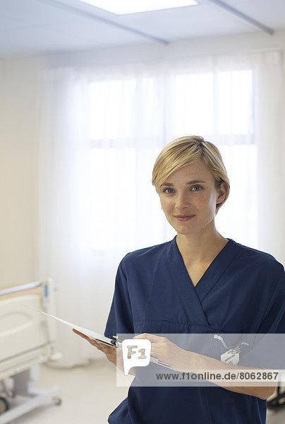 Nurse reading clipboard in hospital hallway