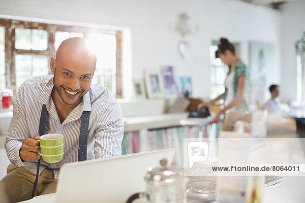 Geschäftsmann mit Laptop beim Frühstück