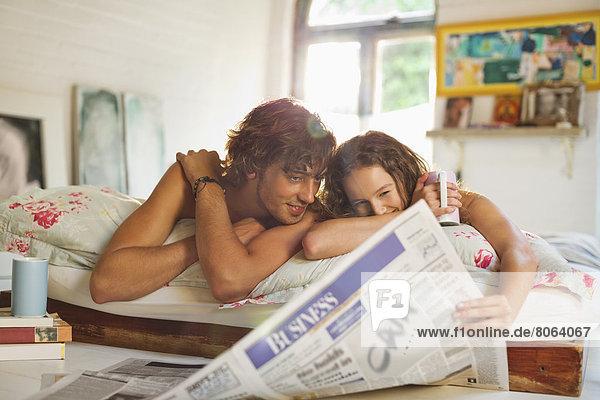Paar liest Zeitung zusammen im Bett