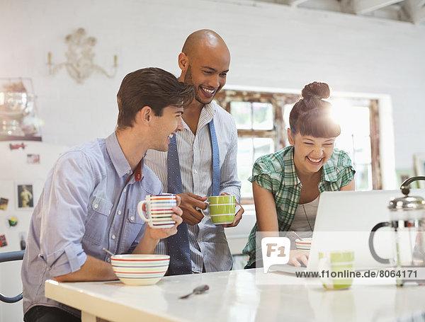 Freunde  die den Laptop beim Frühstück benutzen